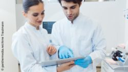 Image: two people in lab coats looking at something on a tablet; Copyright: panthermedia.net/Arne Trautmann